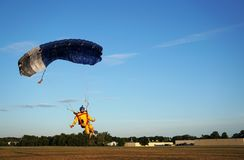 Skydiver under a small blue canopy of a parachute is landing on royalty free stock photos