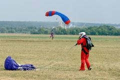 Skydiver unfasten his parachute after landing. Kharkiv, Ukraine - August 26, 2017: Skydiver unfasten his parachute after landing at the airfield Korotych Stock Photo