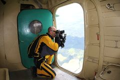 Skydiver is making film from opened door of an airplane. stock image