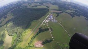 Skydiverflicka som hoppa fallskärm i ovannämnda gräsplanfält för himmel Landskap Extremt flyg stock video