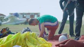 Skydivers подготавливают для полета на землю, человека проверяют оборудование в летнем дне, группе в составе спортсмены видеоматериал
