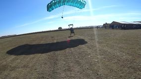 Skydivers flying in tandem with a parachute and landing on the field. Mayskoe, Dnepr, Oktober 14, 2018: Skydivers flying in tandem with a parachute and landing stock footage