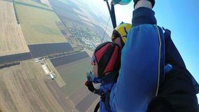 Skydivers flying in tandem under the open parachute. Mayskoe, Dnepr, Oktober 14, 2018: Skydivers flying in tandem under the open parachute. Instructor teaches a stock video footage