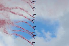 Skydivers in formation. Skydivers with union jack parachutes and red smoke trails Stock Images