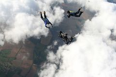 Skydivers in freefall. Three freefalling skydivers in formation high above the clouds Royalty Free Stock Photography