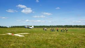 Skydivers gaat naar de vliegtuigen op het gebied royalty-vrije stock afbeelding