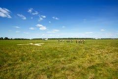 Skydivers gaat naar de vliegtuigen op het gebied stock afbeelding