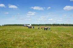 Skydivers gaat naar de vliegtuigen op het gebied stock afbeeldingen