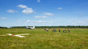 Skydivers go to the aircraft on the field. Paratroopers are boarding the plane Royalty Free Stock Image