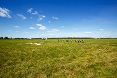 Skydivers go to the aircraft on the field. Paratroopers are boarding the plane Stock Image