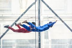 Skydivers in indoor wind tunnel, free fall simulator. Two skydivers in indoor wind tunnel, free fall simulator Royalty Free Stock Images