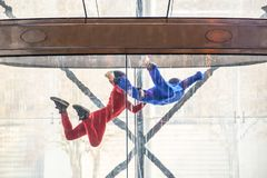 Skydivers in indoor wind tunnel, free fall simulator. Two skydivers in indoor wind tunnel, free fall simulator Stock Image