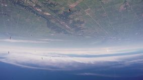 Skydivers jump from airplane falling in sky. Above green land. Clouds. Extreme. Skydivers jump from airplane falling in sky. Above green land. Clouds. Extreme stock video footage