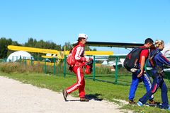 Skydivers listos para saltar y para ir a los aviones contra un avión amarillo fotos de archivo