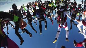 Skydivers make formation in blue sky. Height. Extreme sport. Sunny day. Falling stock footage
