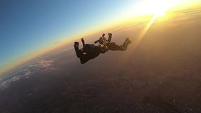 Skydivers make a formation skydive at the sunset