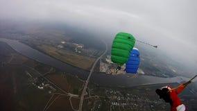 Skydivers med färgrikt hoppa fallskärm flugan över grönt fält i molnig himmel extremt lager videofilmer