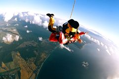 Skydivers over coast. Aerial view of skydivers with parachute cord falling to earth over ocean Stock Images