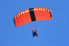 Skydivers que se lanzan en paracaídas abajo a la tierra en salto en tándem Imagenes de archivo