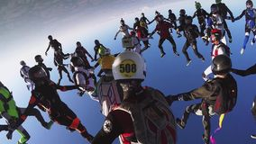 Skydivers team in uniform falling in sky. Create big formation. Extreme stunt. Falling stock video footage