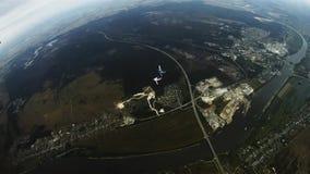 Skydivers trzyma ręki w chmurnym niebie, komarnica nad flatland formacja ekstremum zbiory