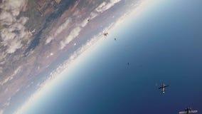 Skydiversteam springen vom Flugzeug, machen Bildung im Himmel Schwestern, die Hände anhalten drehzahl stock video footage