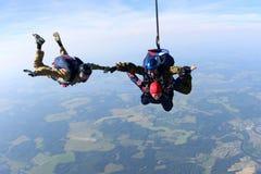 skydiving 一前一后和运动员夹住在天空的手 库存图片