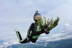 skydiving 有花的女孩在天空的 免版税库存图片