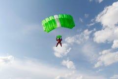 skydiving Ein grüner Fallschirm und ein roter Skydiver sind im Himmel lizenzfreies stockfoto