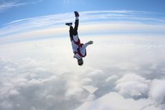 skydiving El Skydiver en la posición de abajo principal se está cayendo sobre las nubes imagen de archivo