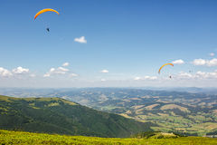 Skydiving  extreme over the mountains. Three persones skydiving  flying over the mountains. parachute extreme sport Stock Images