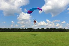 Skydiving. A girl is landing on the green field. stock images