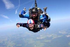 Skydiving het achter elkaar Twee kerels hebben pret in de hemel stock afbeelding