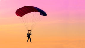 Skydiving. Parachutist flying into the sunset Stock Photo