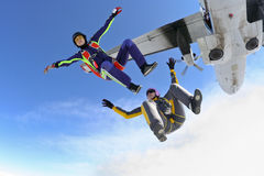 Skydiving photo. Two girls jump out of an airplane royalty free stock photo