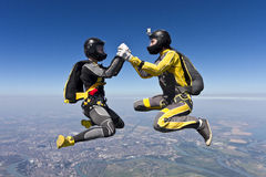 Skydiving photo. Two girls building a figure in a free fall stock photos