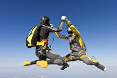 Skydiving photo. Two girls building a figure in a free fall royalty free stock images