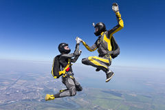 Skydiving photo. Two girls holding hands parachutist stock image