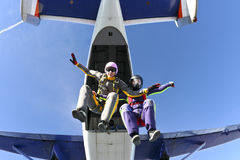 Skydiving photo. Two girls skydivers jump out of an airplane royalty free stock images