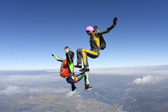 Skydiving photo. Two girls skydivers building freefall in the figure royalty free stock images