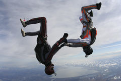 Skydiving photo. Two parachutists perform fall hand in hand upside down royalty free stock photos