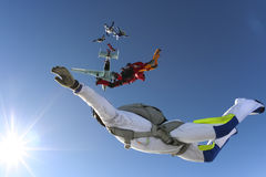 Skydiving photo. A group of paratroopers jumping out of the plane and build a figure stock photo