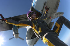 Skydiving photo. The girl parachutist jumps out of an airplane and fly freestyle stock photo