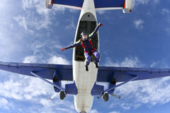Skydiving photo.. The girl parachutist jumps out of an airplane stock photos