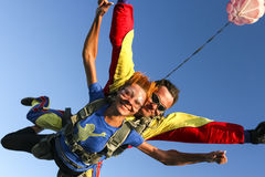 Skydiving photo. Tandem. Tandem jump. The girl with the instructor in freefall royalty free stock images