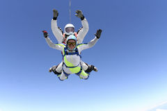 Skydiving photo. Tandem. Tandem jump. The girl with the instructor in freefall royalty free stock photography