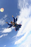 Skydiving photo. Tandem jump. Tandem jump in the sky with clouds royalty free stock images