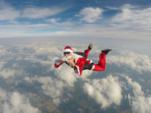 Skydiving Santa christmas. Radical Santa practicing extreme sports Royalty Free Stock Photo
