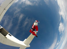 Skydiving Santa jump from the plane. Radical Santa practicing extreme sports Stock Photo