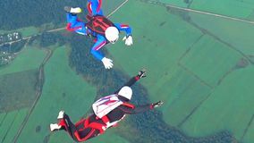 Skydiving. On a sunny summer day, parachutist athletes show performances in the sky stock video footage
